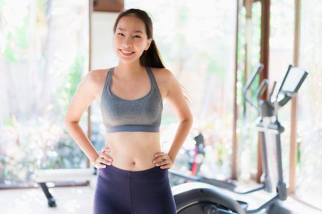 Schöne junge asiatische frauenübung des porträts mit eignungsausrüstung im turnhalleninnenraum