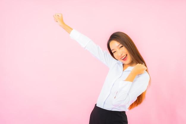 Schöne junge asiatische geschäftsfrau des porträts mit aktionsrosa lokalisierter wand