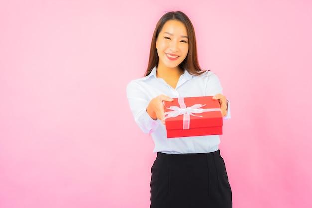 Schöne junge asiatische geschäftsfrau des porträts mit roter geschenkbox auf rosa farbwand