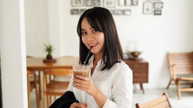 Schöne junge asiatische geschäftsfrau im anzug stehend, die braune kaffeetasse im kaffee hält, während eine kaffeepause hat.