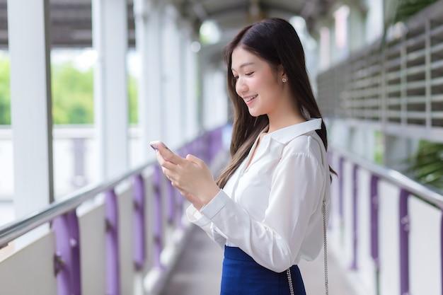 Schöne junge asiatische geschäftsfrau steht auf der überführung des skytrain im freien in der stadt, während sie ihr smartphone verwendet, um nachrichten an das büro zu senden.