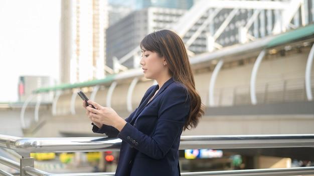 Schöne junge asiatische geschäftsfrau verwendet smartphone in der modernen stadt