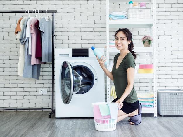Schöne junge asiatische hausfrau der frau, die flüssiges waschmittel, blaue flasche mit dem lächeln und betrachten der kamera nahe der waschmaschine im waschraum sitzt und hält.