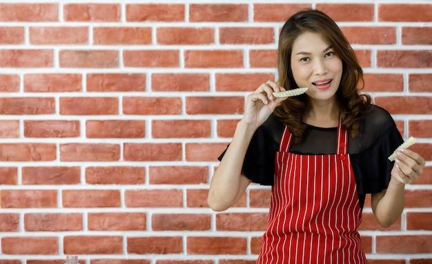 Schöne junge asiatische hausfrau in rot gestreifter schürze, die lustig kartoffeln zu ihrem lächelnden gesicht aufhebt, bevor sie gebratenes essen in der nähe einer backsteinmauer in der küche mit einem glas öl, einer pfanne und einem gasherd kocht