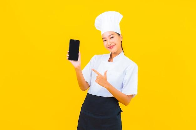 Schöne junge asiatische kochfrau des porträts mit intelligentem handy auf gelbem lokalisiertem hintergrund