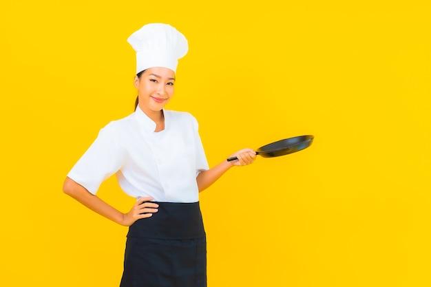 Schöne junge asiatische kochfrau des porträts mit schwarzer wanne auf gelbem lokalisiertem hintergrund