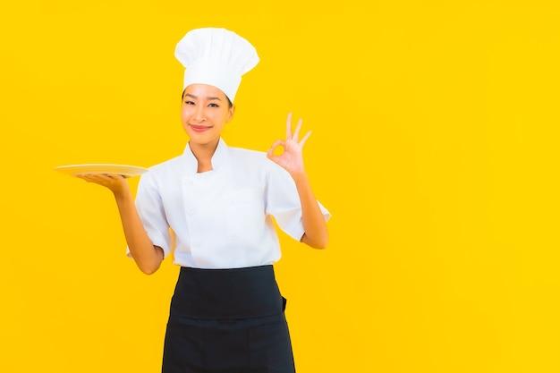 Schöne junge asiatische kochfrau des porträts mit teller auf gelbem lokalisiertem hintergrund