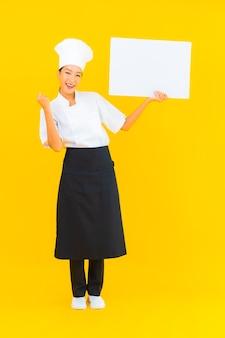 Schöne junge asiatische kochfrau des porträts mit weißer leerer anschlagtafel auf gelbem lokalisiertem hintergrund