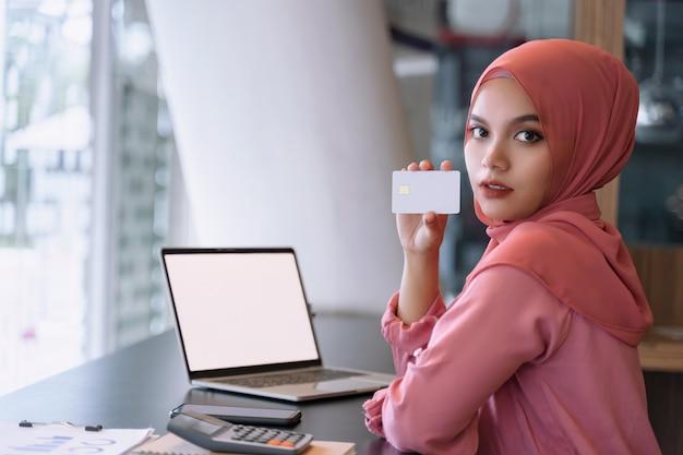Schöne junge asiatische moslemische geschäftsfrau im rosa hijab und in der freizeitkleidung mit dem laptop und händen des weißen schirmes, die eine weiße leere kreditkarte zeigen