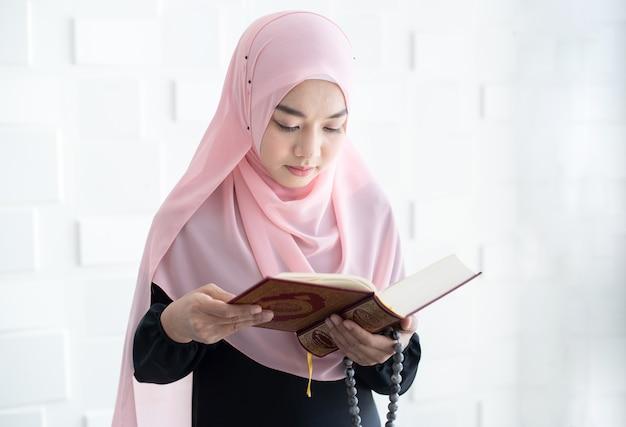 Schöne junge asiatische muslimische frau, die koran liest