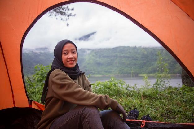Schöne junge asiatische muslimische frau genießen camping im zelt