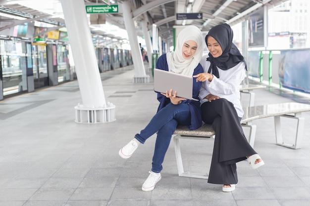 Schöne junge asiatische person des mädchens zwei, die an einem skytrain mit einem laptop arbeitet. muslimische frauen