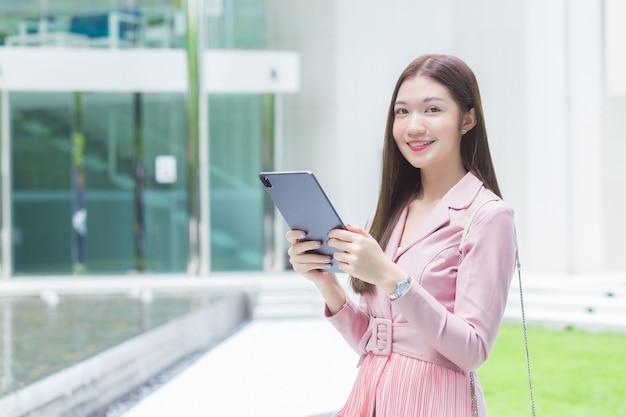 Schöne junge asiatische professionelle geschäftsfrau mit langen haaren lächelt draußen im garten vor dem büro, während sie das tablet in der hand hält, um sich mit kunden im büro zu treffen,