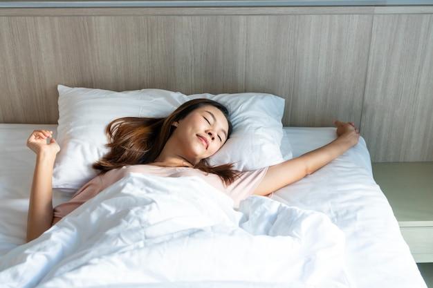 Schöne junge asiatische reisende frau, die nach dem aufwachen mit sonnenaufgang am morgen im schlafzimmer am hotel streckt