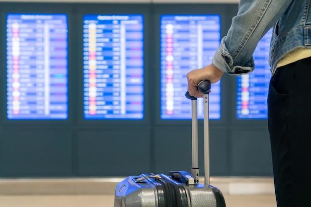 Schöne junge asiatische touristenfrau mit rucksack, handgepäck im internationalen flughafen, das fluginformationstafel betrachtet