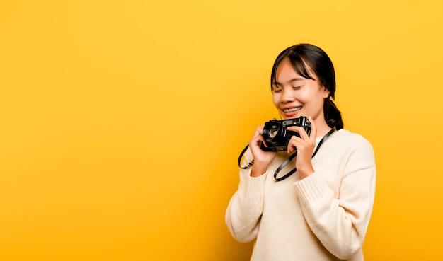 Schöne junge asiatische touristische studioaufnahme mit der kamera in der hand isoliert auf gelbem hintergrund. fotografie-konzept