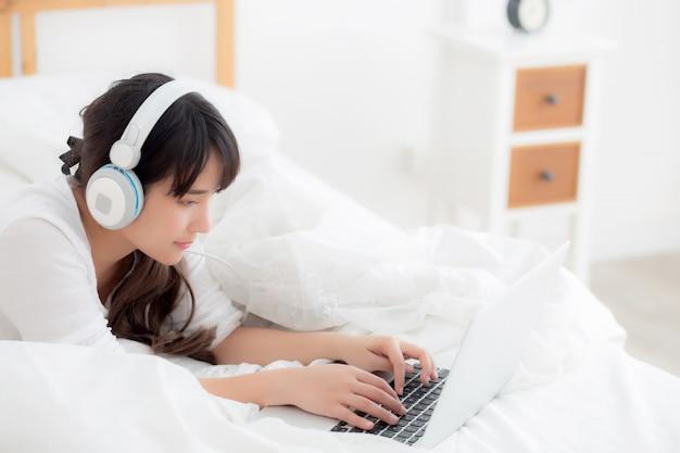 Schöne junge asien-frau, die im schlafzimmer unter verwendung des laptops liegt