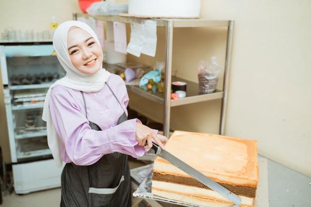 Schöne junge bäckerin, die kuchen an ihrer küche macht. junger asiatischer muslimischer kuchenmacher