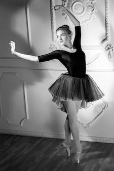 Schöne junge ballerina, die mit ballett-tutu im schattenbildstudio auf weißem hintergrund tanzt