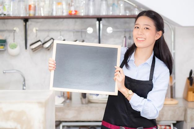 Schöne junge barista asiatische frau des porträts ist ein angestellter, der tafel halten steht.