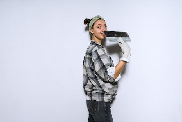 Schöne junge baumeisterin, die reparaturen durchführt und einen spachtel in den händen hält