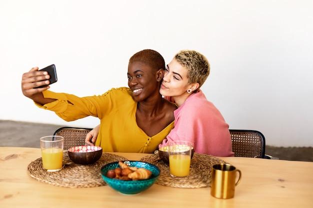 Schöne junge bestfriend-frauen, die selfie mit einem smartphone nehmen und lächeln, während sie zu hause frühstücken