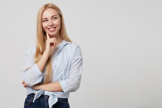 Schöne junge blonde dame in der freizeitkleidung, die ihre wange mit zeigefinger hält und freudig beiseite schaut und aufwirft