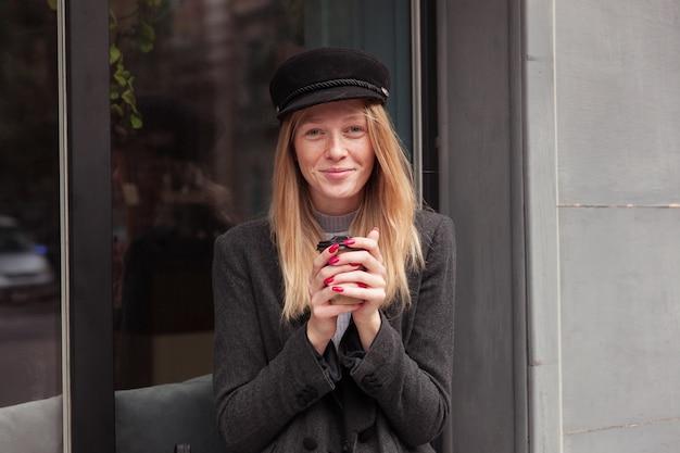 Schöne junge blonde dame mit roter maniküre, die draußen kaffee trinkt, während sie durch stadt geht, gekleidet in elegante kleidung, während sie über caféaußenseite aufwirft