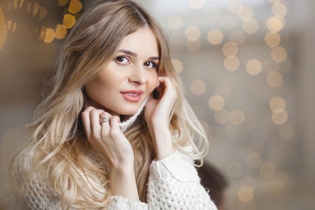 Schöne junge blonde frau auf weihnachten unscharfen lichtern