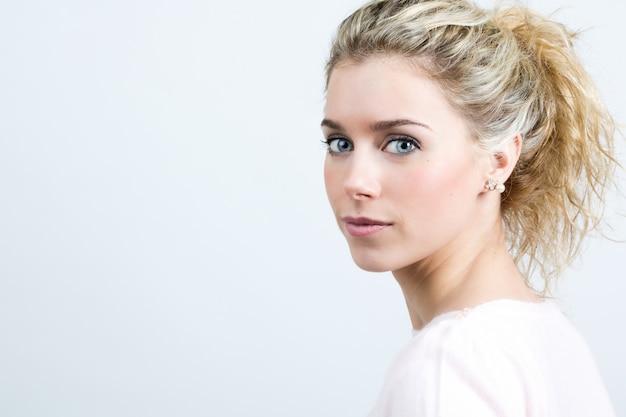Schöne junge blonde frau blick auf die kamera