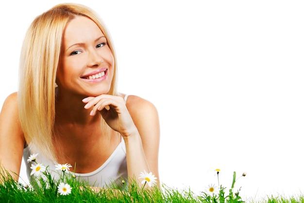 Schöne junge blonde frau, die auf gras mit kamillenblüten liegt, lokalisiert auf weißem hintergrund