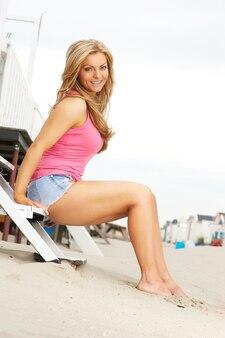 Schöne junge blonde frau, die barfuß am strand sitzt
