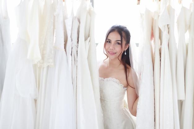 Schöne junge blonde frau, die ein hochzeitskleid wählt. lächelnde asiatische dame, die das hochzeitskleid der handbraut in der umkleidekabine im ladengeschäft hält. konzept schöne liebe glücklichen besten tag.
