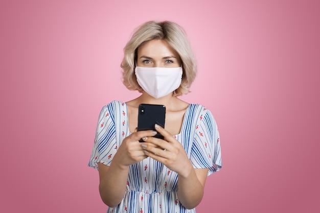 Schöne junge blonde frau, die ein kleid und eine medizinische maske trägt, plaudert auf handy, das kamera an einer rosa wand lächelt