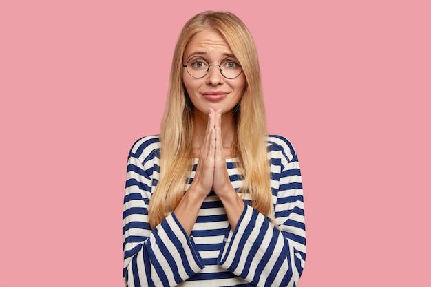 Schöne junge blonde frau, die gegen die rosa wand aufwirft