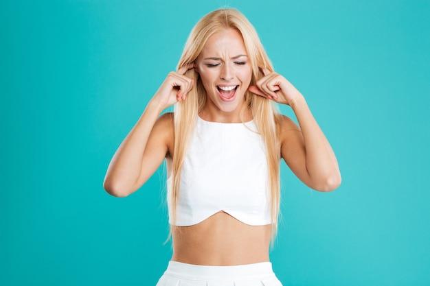 Schöne junge blonde frau, die ihre ohren mit den fingern bedeckt, die auf dem blauen hintergrund lokalisiert werden