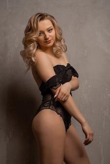 Schöne junge blonde frau, die im schwarzen spitzenbodysuit im studio nahe der wand aufwirft.