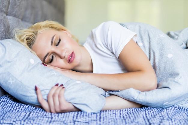 Schöne junge blonde frau, die in einem bett zu hause schläft