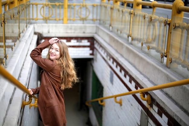 Schöne junge blonde frau, die lächelt, während sie auf der treppe posiert, die zum untergrund führt