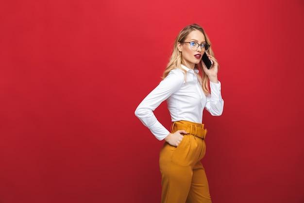 Schöne junge blonde frau, die lokal über rotem hintergrund steht und handy hält