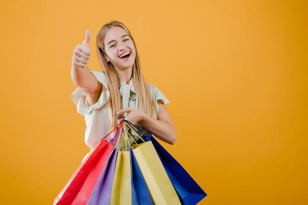 Schöne junge blonde frau, die mit den bunten einkaufenbeuteln getrennt über gelb lächelt