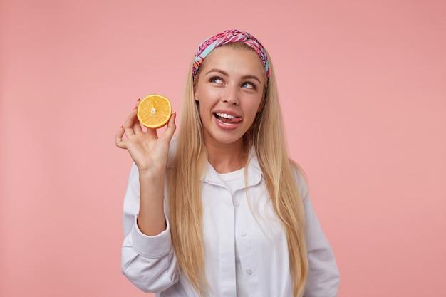 Schöne junge blonde frau, die mit orange in der hand aufwirft, zunge herauszieht und beiseite schaut, lässige kleidung tragend