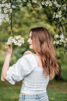 Schöne junge blonde frau, die nahe dem apfelbaum steht.