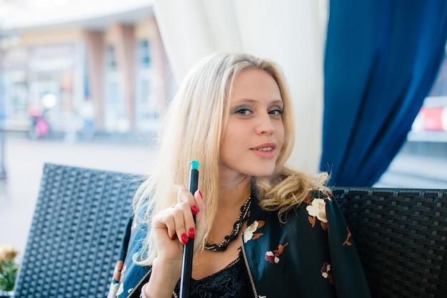 Schöne junge blonde frau, die shisha im straßencafé raucht