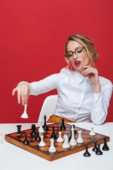Schöne junge blonde frau, die weißes hemd sitzt, das am tisch sitzt und schach lokalisiert über rotem hintergrund spielt
