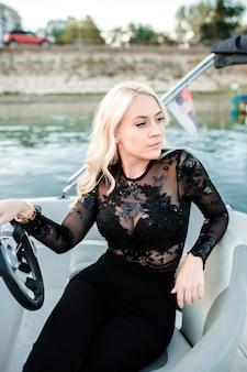 Schöne junge blonde frau, ein boot auf dem wasser reitend.