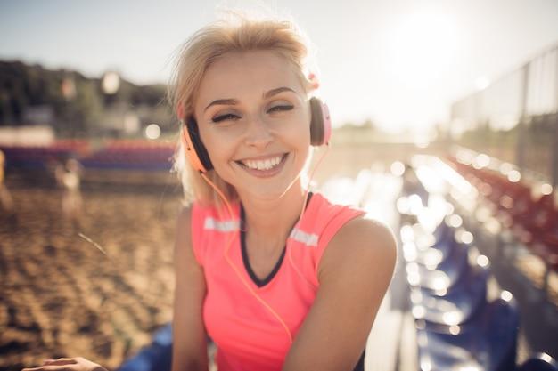 Schöne junge blonde frau im rosa bunten anzug, der musik auf kopfhörern am strand hört