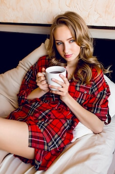 Schöne junge blonde frau im rot karierten hemd entspannte sich in ihrem bett am morgen, trank tee und träumte.