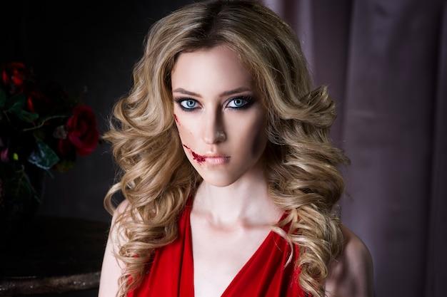 Schöne junge blonde frau im roten kleid mit halloween-make-up und blutiger gesichtskunst, vintages interieur