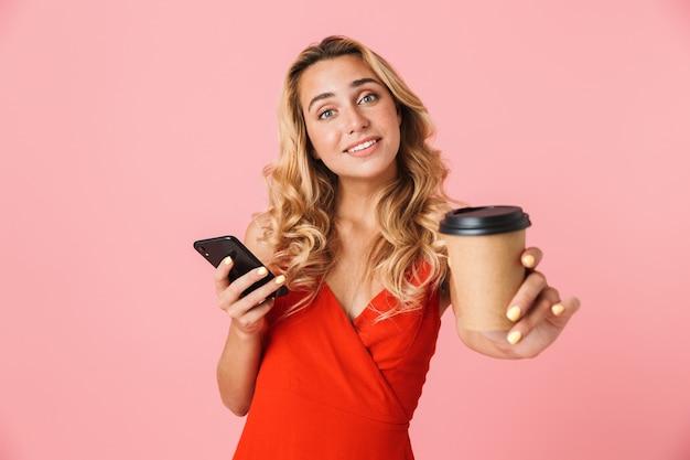 Schöne junge blonde frau im sommerkleid, die isoliert über rosa wand steht und das handy benutzt, während sie eine tasse zum mitnehmen zeigt